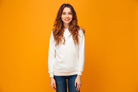 Smiling brunette woman in sweater posing and looking at the camera over yellow background Banco de Imagens - 97776068