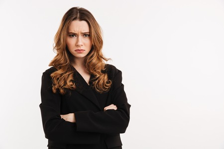 Portrait of an upset young woman dressed in black jacket standing with arms folded isolated over white background Stock Photo