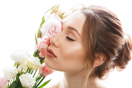 Beauty portrait of nude woman with brown hair in bun holding branch of blossom lisianthus flowers with closed eyes isolated over white background