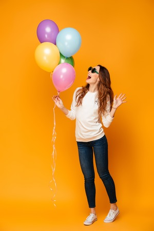 Full length image of Cheerful brunette woman in sweater and sunglasses holding balloons and rejoices over yellow background