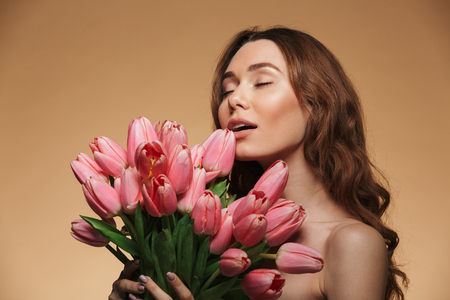 Beautiful woman 20s with natural makeup taking pleasure with closed eyes while holding bouquet of tulips isolated over beige background Stock fotó