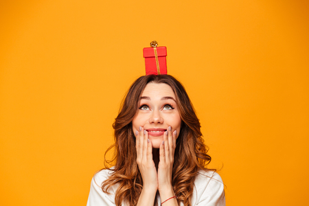 Pleased brunette woman in sweater holding small gift box on head and looking up over yellow background