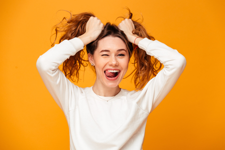 Cheerful brunette woman in sweater holding her hair and showing tongue while winks and looking at the camera over yellow background