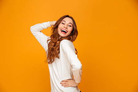 Cheerful brunette woman in sweater posing with arm on hip and looking at the camera over yellow background Imagens