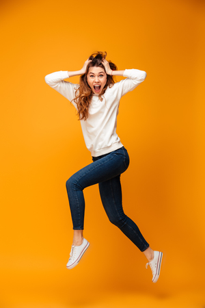 Full length image of Shocked brunette woman in sweater jumping while holding her head and looking at the camera over yellow background