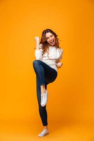 Full length image of Happy brunette woman in sweater screaming and rejoices while looking at the camera over yellow background