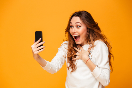Surprised brunette woman in sweater using smartphone while rejoices over yellow background