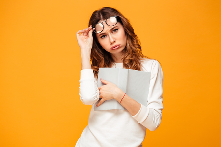 Upset brunette woman in sweater take off eyeglasses and looking at the camera while hugging book over yellow background Imagens