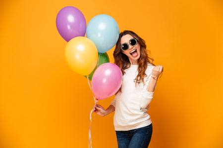 Happy screaming brunette woman in sweater and sunglasses holding balloons while rejoices and looking at the camera over yellow background