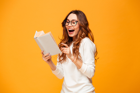Cheerful brunette woman in sweater and eyeglasses reading book over yellow background