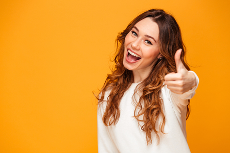 Image of happy young woman standing isolated over yellow background showing thumbs up. Looking camera.