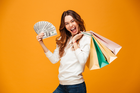 Joyful brunette woman in sweater holding money and packages while looking at the camera over yellow background