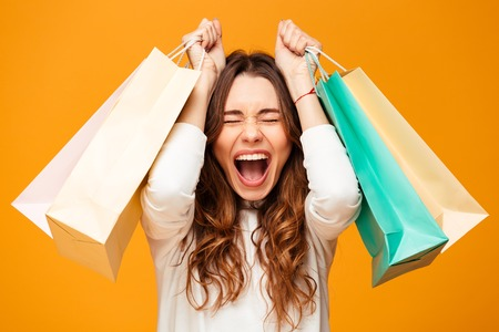 Happy screaming brunette woman in sweater holding packages with closed eyes over yellow background