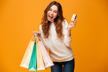 Bild der aufgeregten schreienden Stellung der jungen Frau lokalisiert über dem gelben Hintergrund, der die Kamera hält Einkaufstaschen und Kreditkarte schaut.