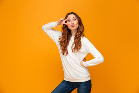 Funny brunette woman in sweater posing with arm on hip while showing peace gesture and looking at the camera over yellow background Stock Photo