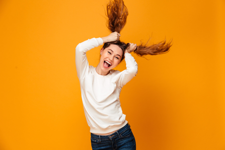 Laughing brunette woman in sweater holding her hair and looking at the camera over yellow background Imagens