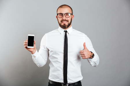 Photo of happy successful man in glasses and tie demonstrating cell phone and showing thumb up isolated over gray background