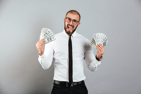Portrait of a happy businessman holding lots of cash isolated over gray background
