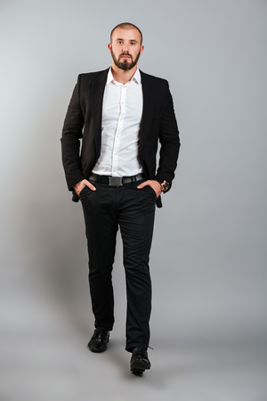 Full-length portrait of serious man in businesslike suit posing on camera with hands in pockets isolated over gray background