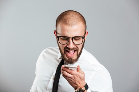Portrait of a mad businessman yelling at mobile phone isolated over gray background Stock Photo
