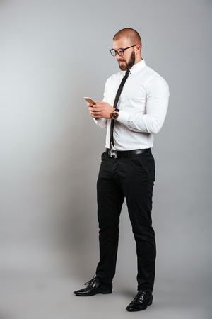 Full-length image of young unshaved man in glasses and tie chatting or working on mobile phone isolated over gray background