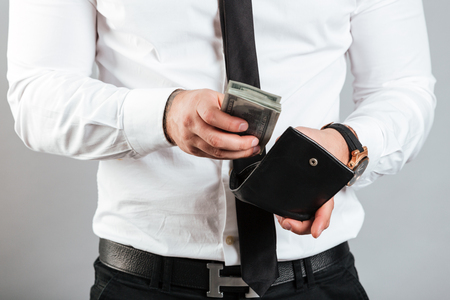 Close up of a rich man putting cash in his wallet isolated over gray background Stock Photo
