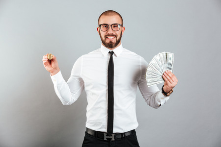 Photo of rich man 30s in glasses and suit showing bitcoin and lots of money dollar currency isolated over gray background Stock Photo
