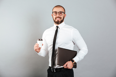 Image of working businessman in glasses and suit holding takeaway coffee and laptop in hands isolated over gray background Stock fotó