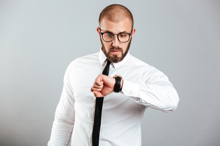 Image of concentrated adult man 30s in business outfit looking on wristwatch isolated over gray background