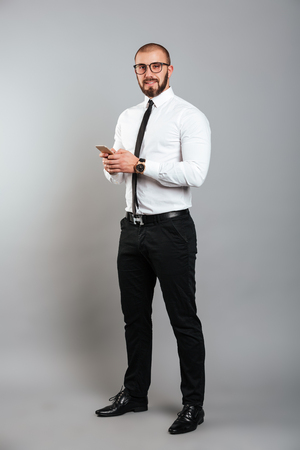 Full-length image of young bearded man in glasses and tie looking on camera with cell phone in hands isolated over gray background
