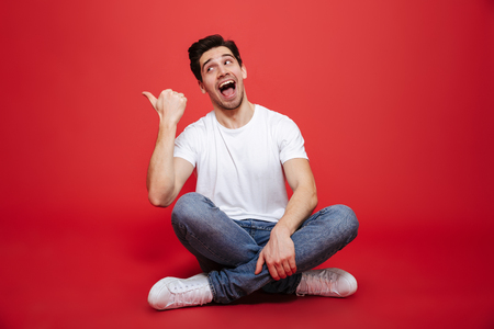 Portrait of a happy young man in white t-shirt sitting on a floor and pointing finger away isolated over red background