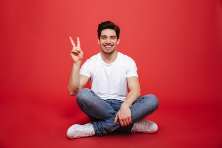 Portrait of a friendly young man in white t-shirt sitting on a floor and showing peace gesture isolated over red background