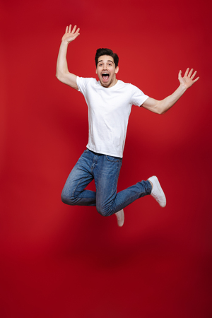 Full length portrait of a happy young man in white t-shirt jumping while celebrating success isolated over red background