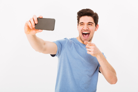 Image of satisfied man with brown hair and bristle smiling and pointing finger on camera while taking selfie on black mobile phone isolated over white background Stockfoto - 97777608