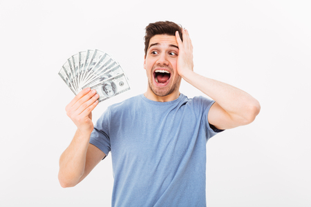Photo of lucky rich guy in casual t-shirt screaming and rejoicing his money prize in cash isolated over white wall