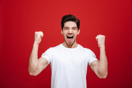 Portrait of a cheerful young man in white t-shirt celebrating success isolated over red background