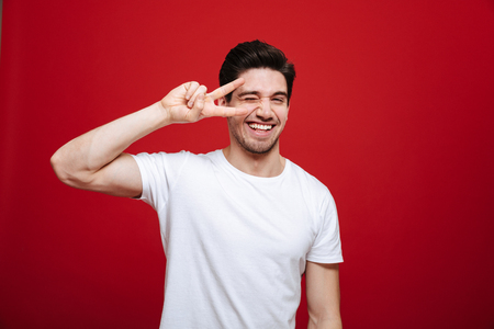 Portrait of a happy young man in white t-shirt showing peace gesture isolated over red background Stockfoto