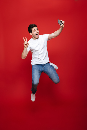 Full length portrait of a cheerful young man in white t-shirt showing peace gesture while taking a selfie and jumping isolated over red background