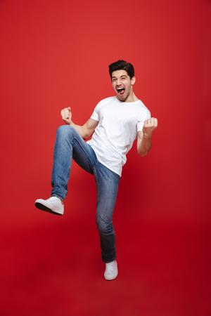 Retrato de cuerpo entero de un joven feliz en camiseta blanca celebrando el éxito aislado sobre fondo rojo.