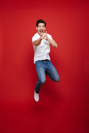 Full length portrait of a happy young man in white t-shirt pointing fingers at camera while celebrating success isolated over red background Foto de archivo
