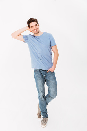 Full-length photo of caucasian attractive man in casual t-shirt and jeans smiling and posing on camera with hand in pocket isolated over white background