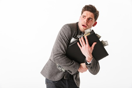Portrait of a terrified young businessman holding briefcase full of money banknotes isolated over white background