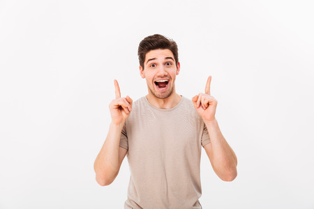 Surprised brunette man 30s wearing beige t-shirt gesturing fingers upward on copyspace with excitement on face isolated over white background