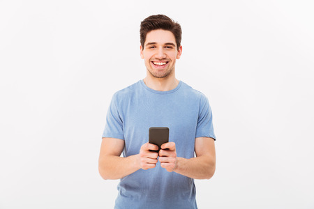 Happy man 30s in casual t-shirt typing sms or browsing internet using mobile phone isolated over white background