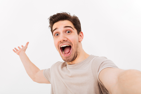 Photo of excited man in casual t-shirt and bristle on face screaming in happiness while taking selfie isolated over white background