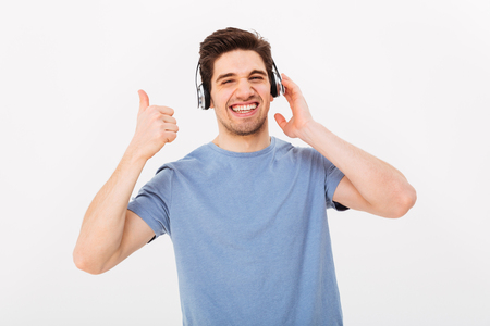 Pleased guy in casual t-shirt listening to music via headphones and gesturing thumb up with smile isolated over white background Stock Photo