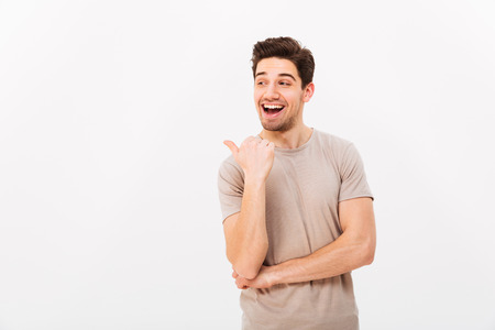 Handsome man 30s with brown hair wearing beige t-shirt gesturing finger aside on copyspace isolated over white background Stockfoto