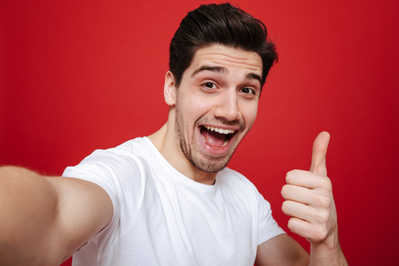 Portrait of a happy young man in white t-shirt showing thumbs up gesture while taking a selfie isolated over red background Stockfoto