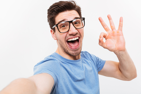 Joyful man in t-shirt and eyeglasses making selfie and showing ok sign while looking at the camera over grey background Reklamní fotografie