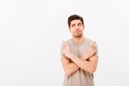 Image of muscular brooding man wearing beige t-shirt gesturing fingers aside with crossed arms on copyspace isolated over white background